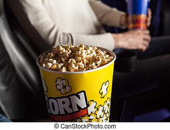 Un cubo de palomitas con un hombre sentado en el teatro
