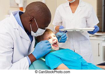 Un dentista afroamericano examinando los dientes del paciente
