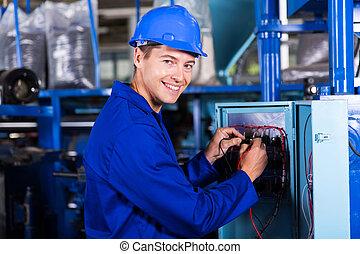 Un electricista masculino trabajando en una máquina industrial