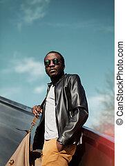 Un elegante joven africano con una chaqueta de cuero negra con una bolsa en la ciudad sobre el cielo de la tarde