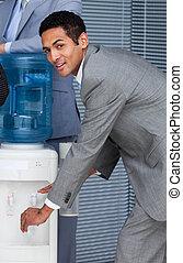 Un empresario atractivo llenando vasos de agua