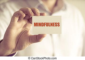 Un empresario con una tarjeta de atención mental