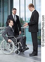 Un empresario discapacitado hablando con sus compañeros