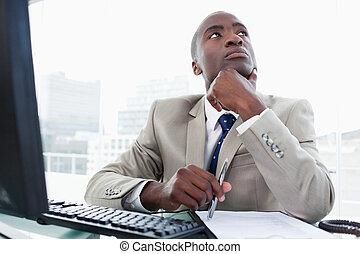 Un empresario pensante trabajando con una computadora