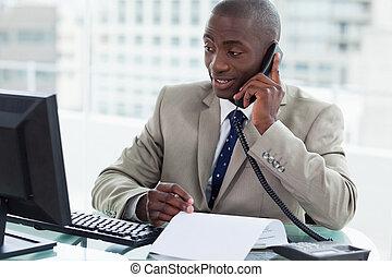 Un empresario sonriente haciendo una llamada mientras mira su computadora en su oficina