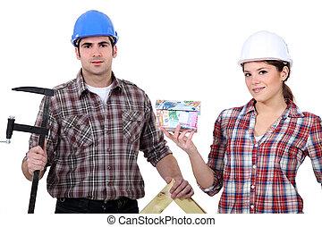 Un equipo de comerciantes sosteniendo sus herramientas y un modelo de casa