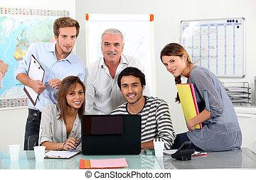 Un equipo joven sentado en una laptop con un tipo mayor