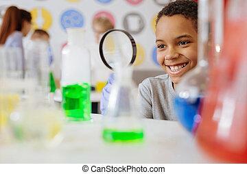 Un escolar optimista sonriendo mientras comprueba el contenido de la petaca química