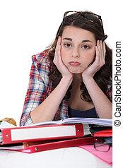 Un estudiante aburrido con un montón de tareas