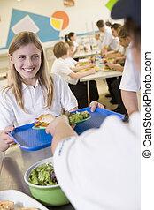 Un estudiante recogiendo el almuerzo de la cafetería de la escuela