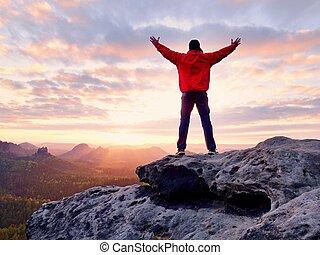 Un excursionista caminando por la cima de la montaña mirando el paisaje de la bella mañana.