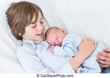 Un feliz niño sonriente sosteniendo a su recién nacido dormido hermanito