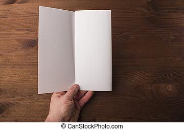 Un folleto en blanco de tres pliegues en mano sobre fondo de madera para reemplazar tu diseño o mensaje