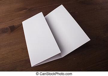 Un folleto en blanco de tres pliegues sobre antecedentes de madera para reemplazar tu diseño o mensaje