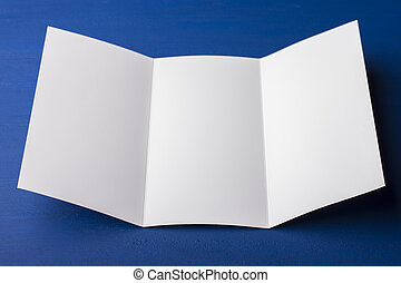 Un folleto en blanco de tres pliegues sobre fondo azul para reemplazar tu diseño o mensaje