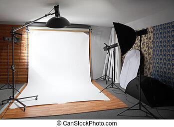 Un fondo blanco dentro del estudio. El cuarto oscuro ilumina grandes lámparas y focos