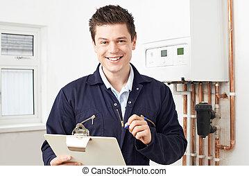 Un fontanero trabajando en una caldera de calefacción central
