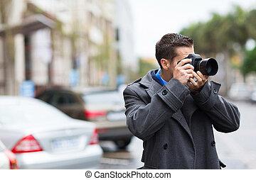 Un fotógrafo joven disparando fotos bajo la lluvia