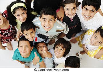 Un gran grupo de niños felices, diferentes edades y razas, multitud