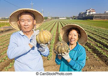 Un granjero asiático con calabaza en su granja