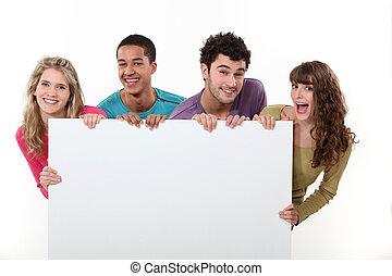 Un grupo de amigos sosteniendo un cartel en blanco