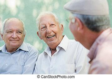 Un grupo de ancianos felices riéndose y hablando