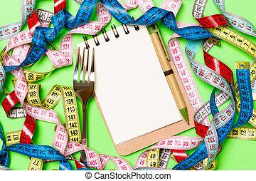 Un grupo de cintas coloridas, bolígrafo, libreta abierta y tenedor en fondo verde con espacio vacío para tu idea. La mejor vista del concepto de estilo de vida saludable