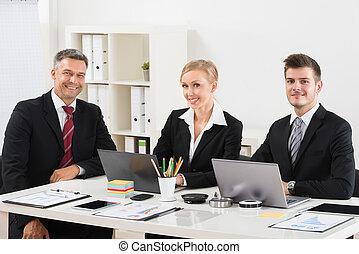Un grupo de empresarios sentados en el escritorio