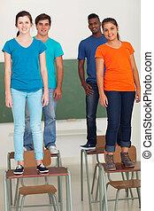 Un grupo de estudiantes de secundaria parados sobre escritorios