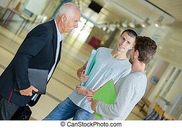Un grupo de estudiantes hablando con el profesor