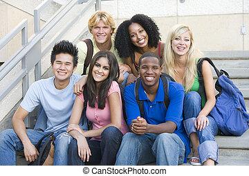 Un grupo de estudiantes universitarios sentados en pasos
