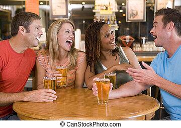 Un grupo de jóvenes amigos bebiendo y riéndose en un bar