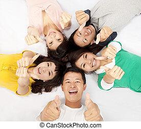 Un grupo de jóvenes asiáticos acostados juntos con el pulgar hacia arriba