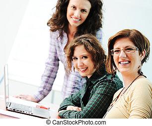 Un grupo de jóvenes felices buscando portátil trabajando en ello