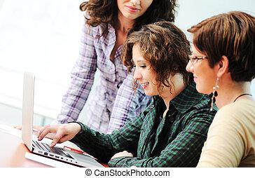 Un grupo de jóvenes felices buscando portátiles trabajando en ello