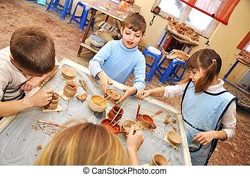 Un grupo de niños con forma de arcilla en el estudio de cerámica