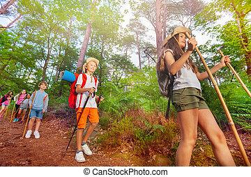 Un grupo de niños exploradores caminan por el bosque