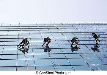 Un grupo de obreros que limpian ventanas en el edificio