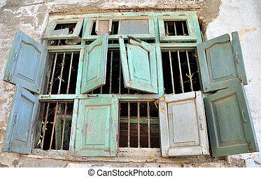 Un grupo de ocho ventanas dilapidadas rotas en una vieja casa