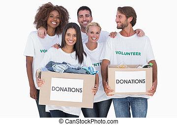 Un grupo feliz de voluntarios sosteniendo cajas de donaciones de ropa
