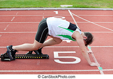 Un hombre atlético en la línea de salida poniendo su pie en el primer bloque de un estadio