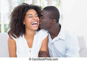 Un hombre atractivo besando a su novia en la mejilla