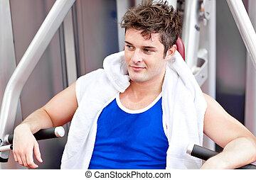 Un hombre atractivo con una toalla sentada