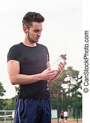 Un hombre bebiendo de una botella de agua durante los deportes