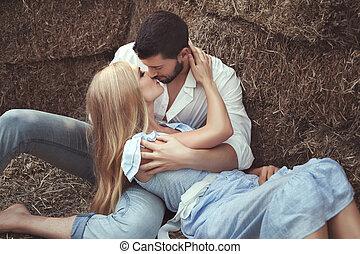 Un hombre besando a una mujer en el pajar.