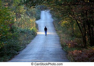 Un hombre caminando solo en la carretera del bosque