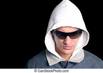 Un hombre con capucha con gafas de sol