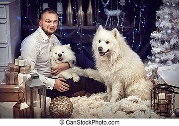 Un hombre con dos perros cerca de un árbol de Navidad