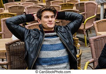 Un hombre con la mano detrás de la cabeza sentado en un restaurante al aire libre