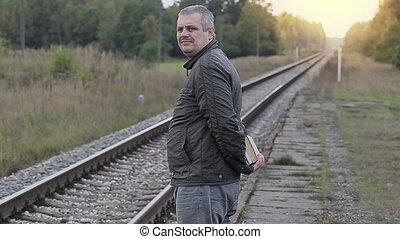 Un hombre con libros esperando el tren